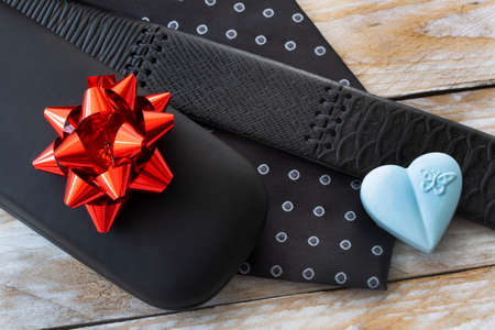 Father's Day Concept. Gift Box with Tie and heart on wooden background. Copy space for text.