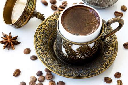 Turkish coffee with roasted coffee beans and traditional copper serving set on white background
