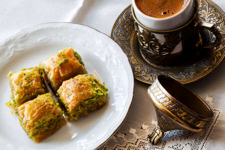 Baklava with walnut and pistachio. Turkish dessert with coffee and traditional copper serving set. Festival of sacrifices. Ramadan holiday.