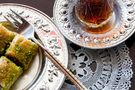 Baklava with walnut and pistachio. Turkish dessert with black arabian tea and traditional silver serving set. Festival of sacrifices. Ramadan holiday.