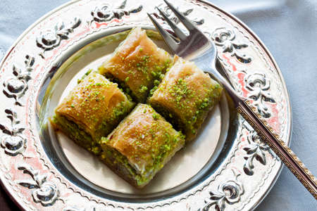 Baklava with walnut and pistachio. Turkish dessert with pistachia and traditional silver serving set. Festival of sacrifices. Ramadan holiday.