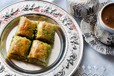 Baklava with walnut and pistachio. Turkish dessert with coffee and traditional silver serving set. Festival of sacrifices. Ramadan holiday.