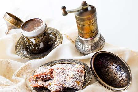 Traditional turkish dessert cezerye and Turkish coffee with coffee grinder.