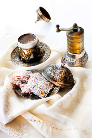 Traditional turkish dessert cezerye and Turkish coffee with coffee grinder. Festival of sacrifices. Feast of Ramadan. Cezerye is made with boiled carrots, sugar, pistachio and coconut. Banque d'images