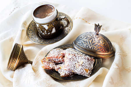 Turkish coffee with traditional turkish dessert cezerye and copper serving set. Feast of Ramadan. Cezerye is made with boiled carrots, sugar, pistachio and coconut. It is located dessert of Mersin.