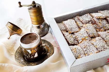 Box of traditional turkish dessert cezerye and Turkish coffee with coffee grinder.