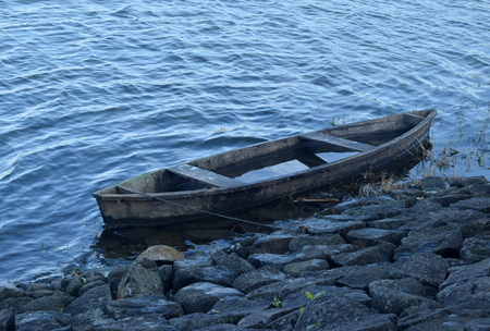 broken boat on the edge of the lake Imagens