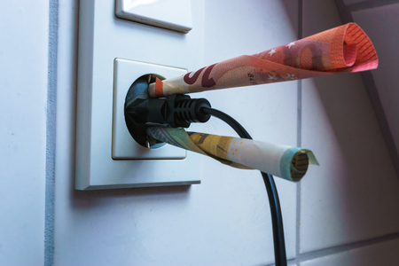 energy savings concept with power socket and money