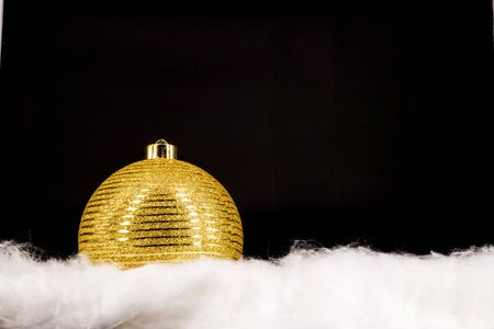 Gold christmas balls with snow isolated on black background