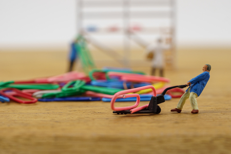 Miniature toy workers carry a paper clip Reklamní fotografie - 90492592