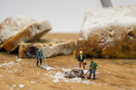 Miniature people shoveling snow from board Stock Photo