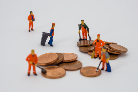 Money laundering concept, miniature people cleaning coins