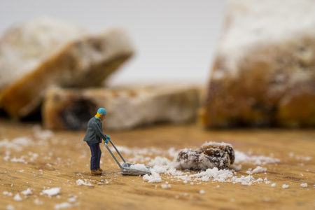 concept Miniature people shoveling snow from board
