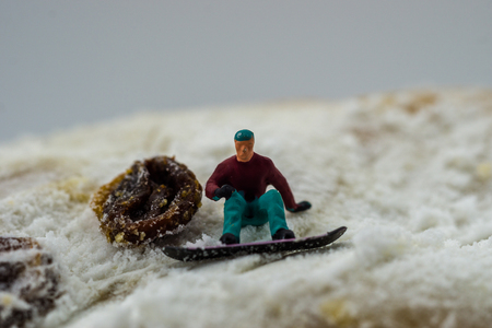 Concept snowboarding on a white mountain with a cake
