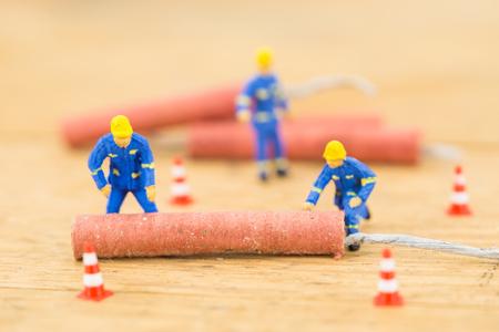 Concept miniature people working hard on Firecracker