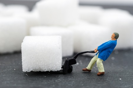 Miniature people Working with sugar. Health care concept.
