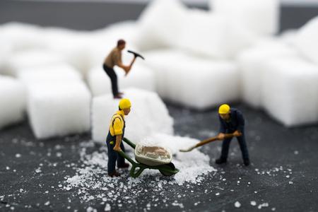 Gente en miniatura trabajando con azúcar. Concepto de salud
