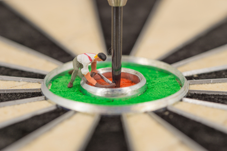 miniature people with dart in bulls eye, close up concept Stock Photo