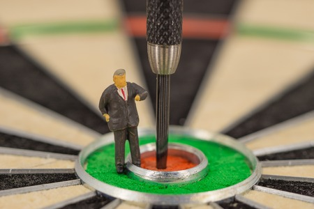 Miniature people with dart in bulls eye, close up concept