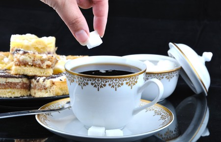 buffet lunch: Hand, wich gives sugar lump to cup of coffee