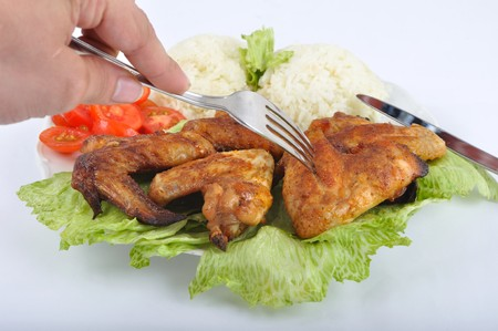 Chicken wings with rice, vegetable and cutlery photo