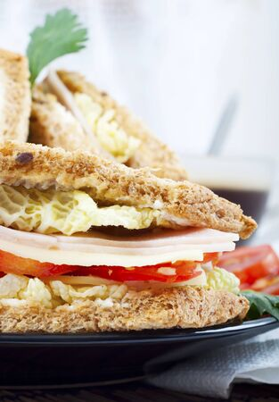 fresh and delicious classic club sandwich over a black glass dish with coffee and vegetable photo