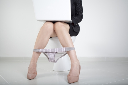 businesswoman legs: Woman working with computer in the bathroom