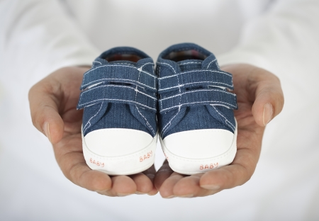 paternity: Man holding baby shoes in white