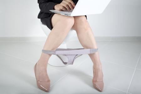 inodoro: Mujer que trabaja en el ordenador en el baño Foto de archivo