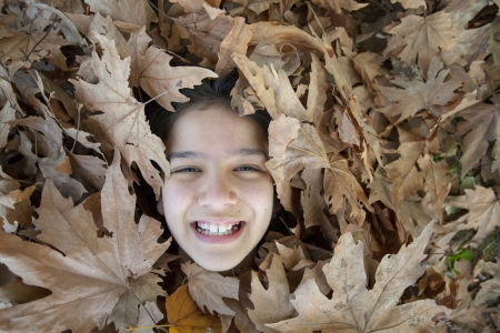 Smiling girl in the leaves