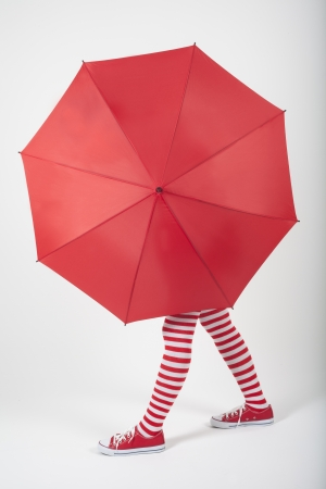 long socks: The girl standing behind a large red umbrella