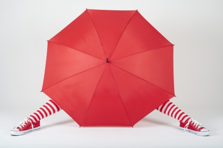 The girl hiding behind a large red umbrella Stock Photo
