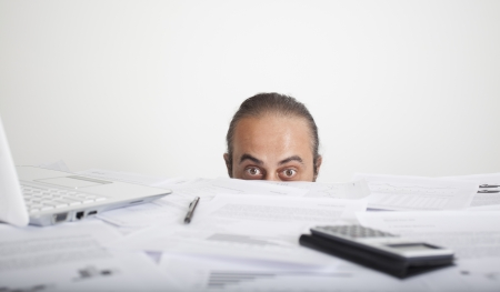 Worried man face looking behind table of office Stock Photo