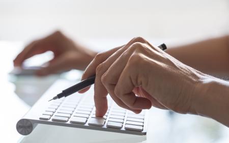 tecla enter: Close-up de manos de la mujer en el teclado de computadora
