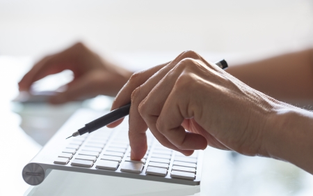 Close-up of woman hands on computer keyboard photo