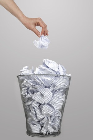 Woman hand throwing crumpled paper into a silver trash bin Stock Photo