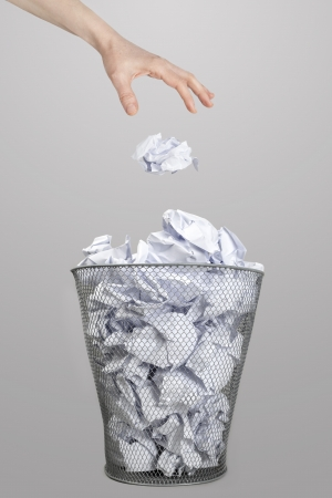 scrunch: The hand of woman throwing crumpled paper into a silver trash bin