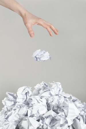 Stack of crumpled paper balls and hand