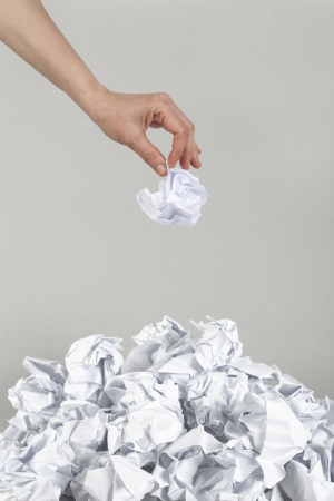 Stack of crumpled paper balls and hand on gray