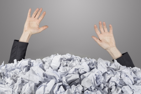 Hands reach out from big heap of crumpled papers photo
