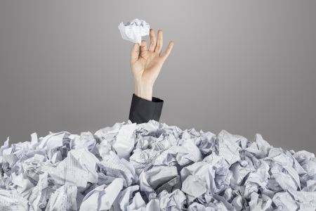 Person under pile of documents with hand holding a crumpled paper photo