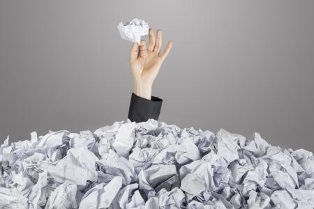 Persona sotto pila di documenti con mano che tiene una carta spiegazzato Archivio Fotografico