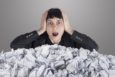 Businesswoman with lot of crumpled paper