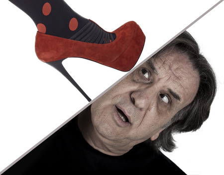 A woman�s foot crushing man�s head photo