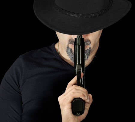 gangster with gun: The man in black holding a gun Stock Photo