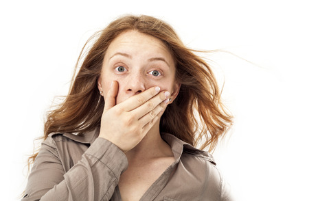 hands in mouth: Surprised young woman Stock Photo