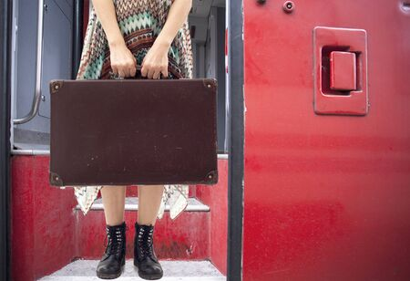 Young woman standing with suitcase on train
