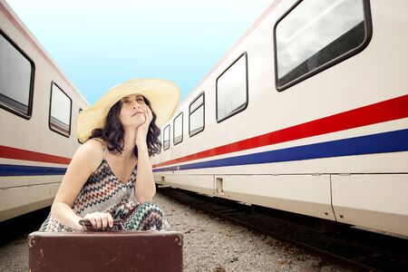 Young woman sitting with suitcase