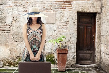 Junge Frau, die mit Koffer