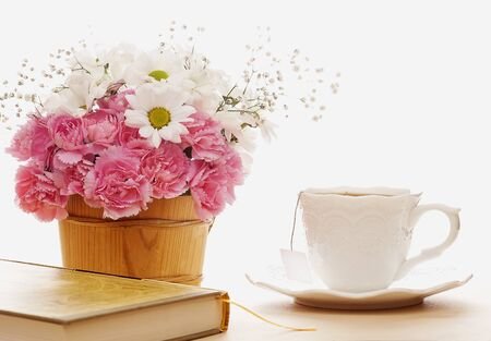 Bouquet of beautiful flowers with a cup and book Stock Photo